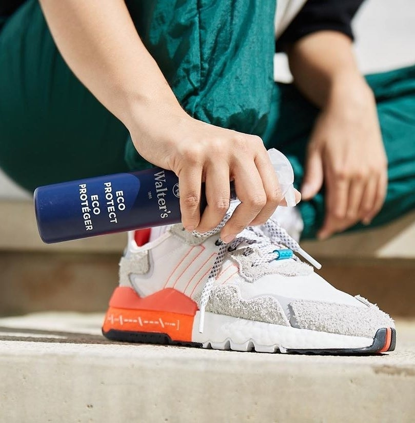 A person spraying their shoes with the solution