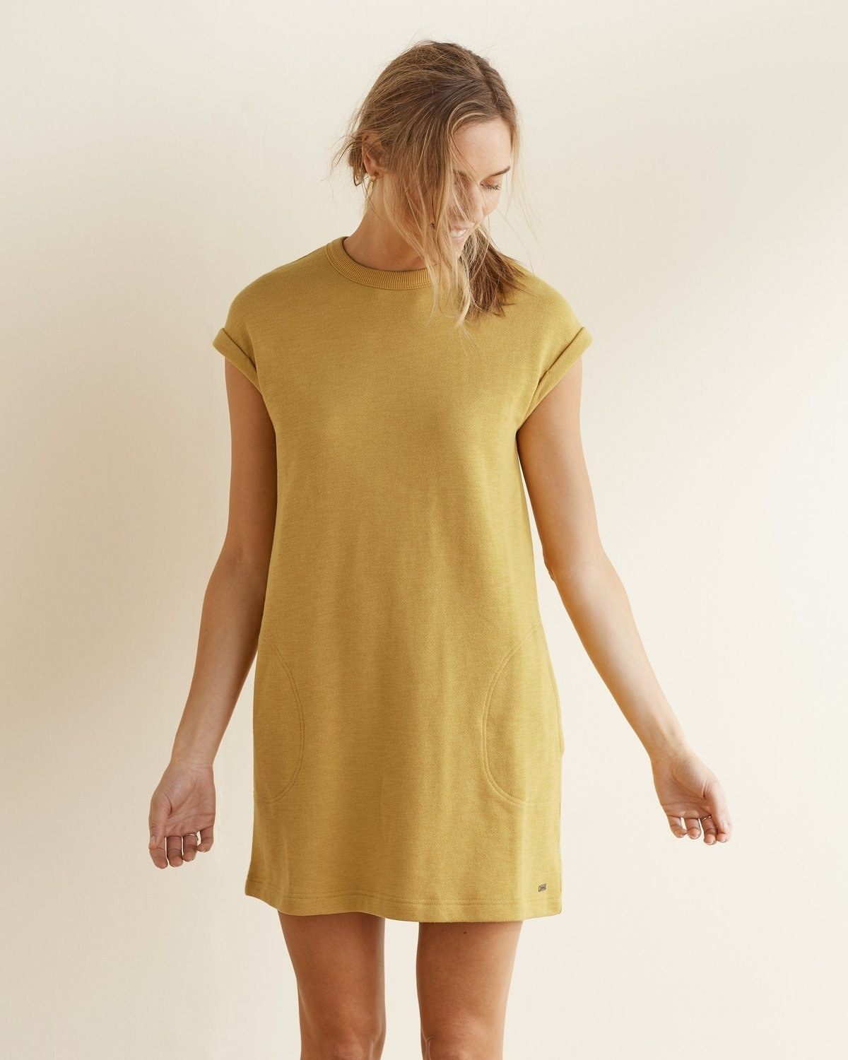 model wears yellow shift dress with short sleeves
