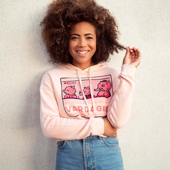 model wears pink hoodie with illustration of animals waiting in line