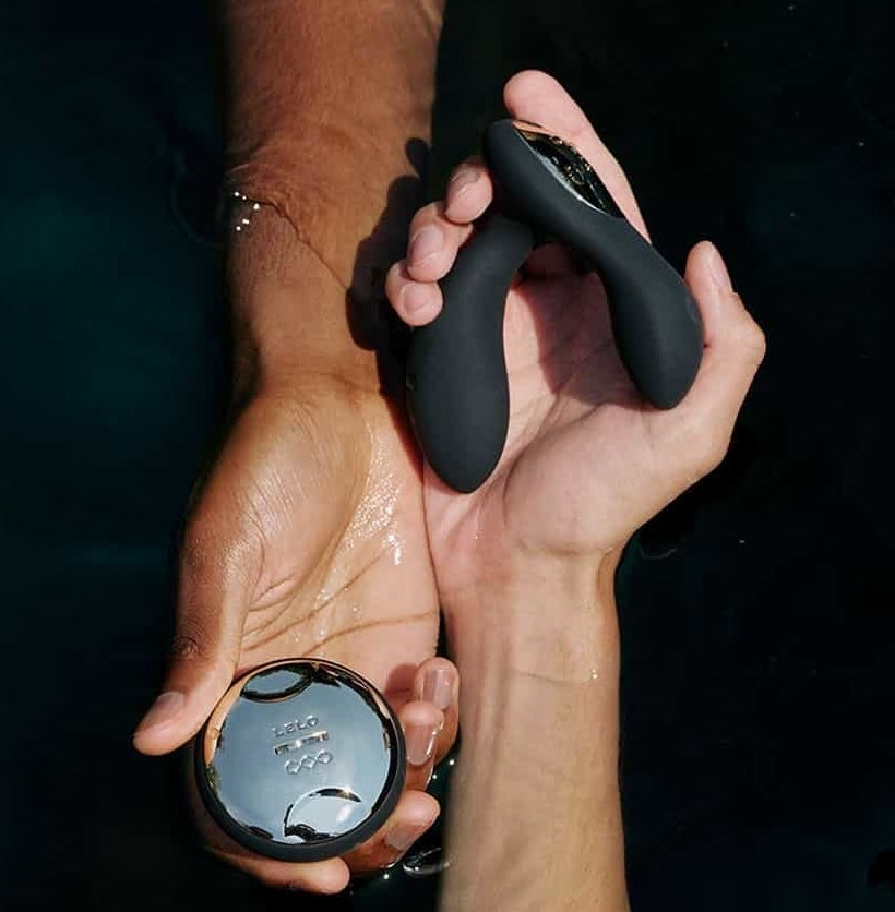 Two hands holding the prostate massager and remote control