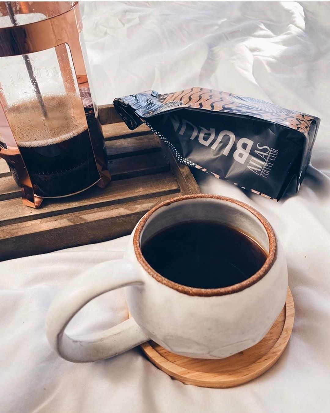 A cup of brewed coffee next to a french press