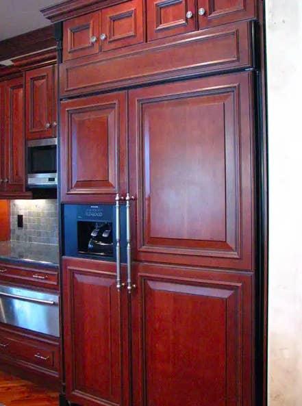 A dark cherry wood paneled fridge