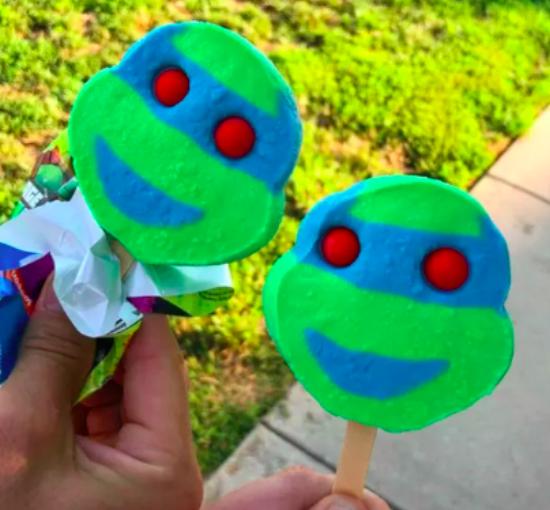 Two hands holding Teenage Mutant Ninja Turtles ice cream pops