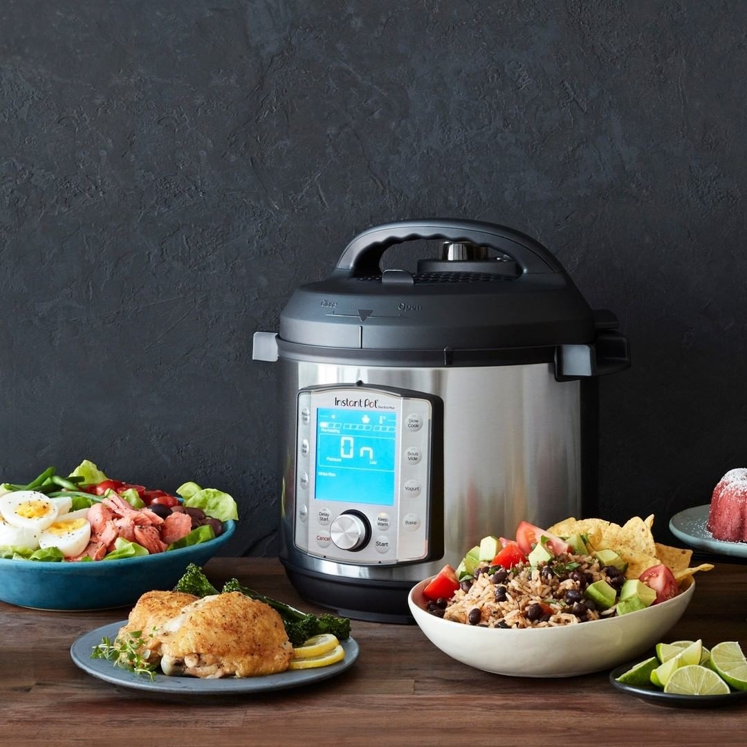 The Instant Pot on a wooden counter with three plates of food around it