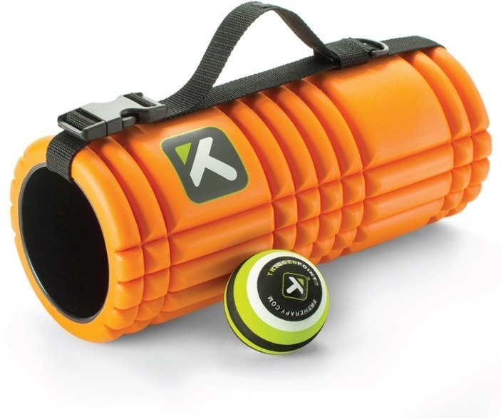 Orange textured foam roller with yellow massage ball next to it