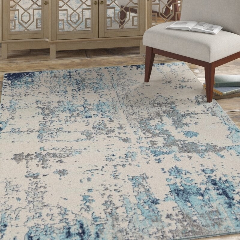 A rug with a blue, gray, and beige print sitting in a room with an accent chair and dresser