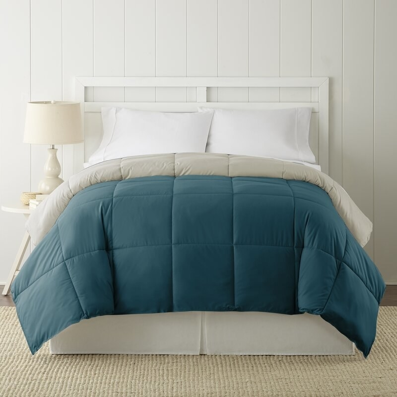 A comforter on the bed with its blue side facing up