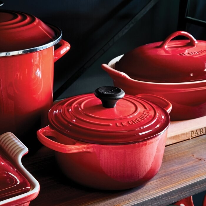 A circular, red Dutch oven with its lid covering it sitting beside other red dishes
