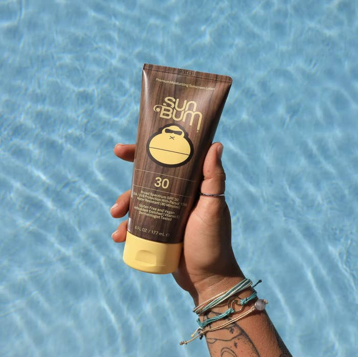 a model holding the brown and yellow squeeze bottle of SPF 30 sunscreen