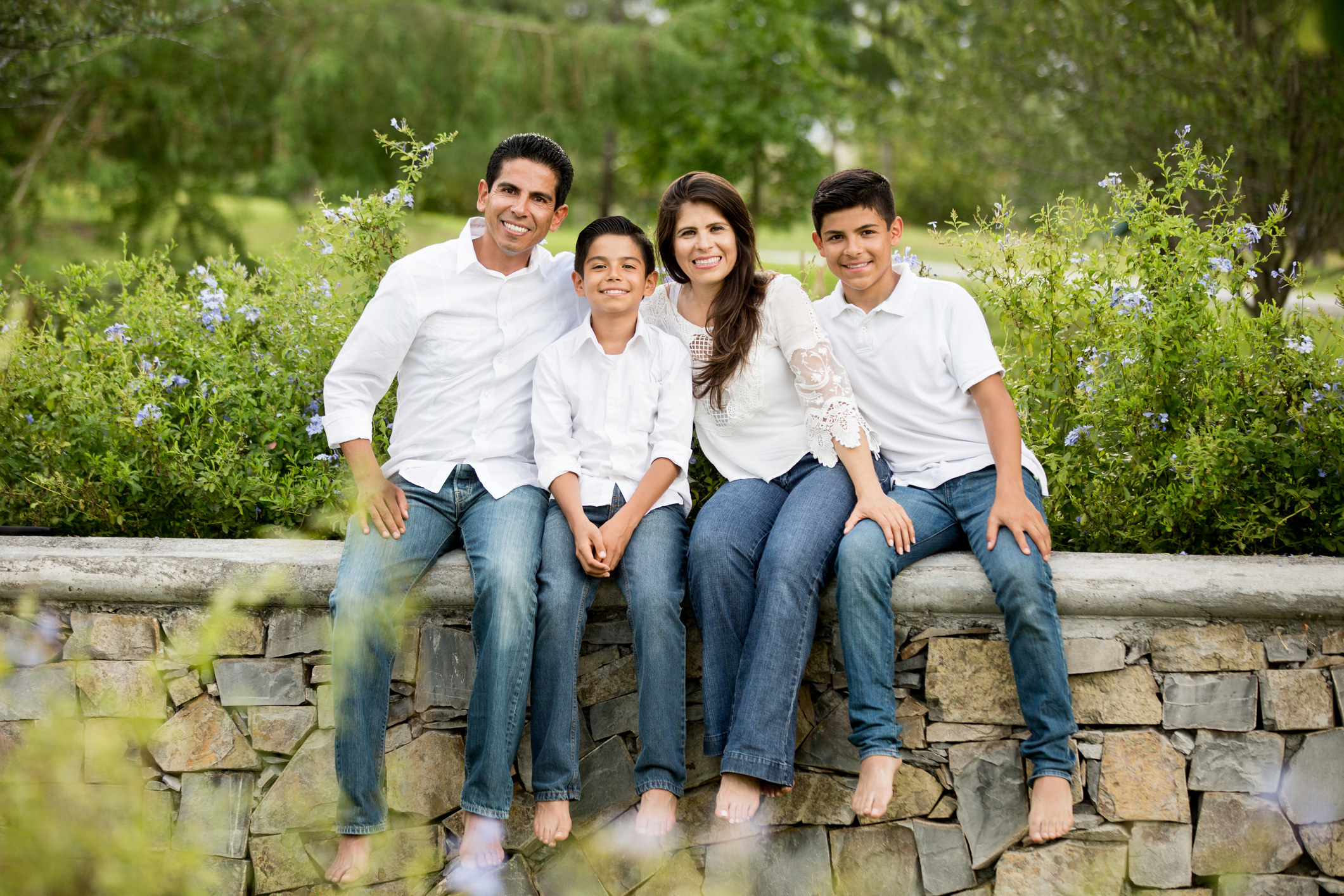 A photo of a family mom, dad, and two sons all wearing blue jeans and white shirts