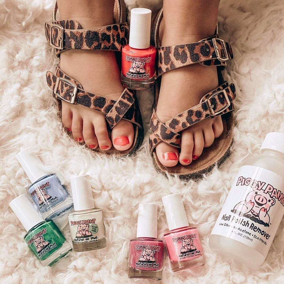 kid's feet in sandals with six different colors of nail polish