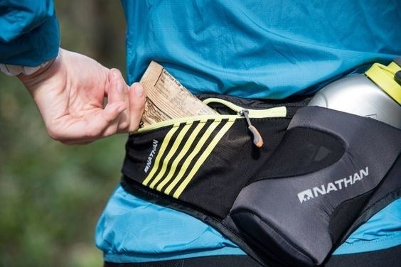 hand pulls snack bar out of black and yellow water bottle waist pack