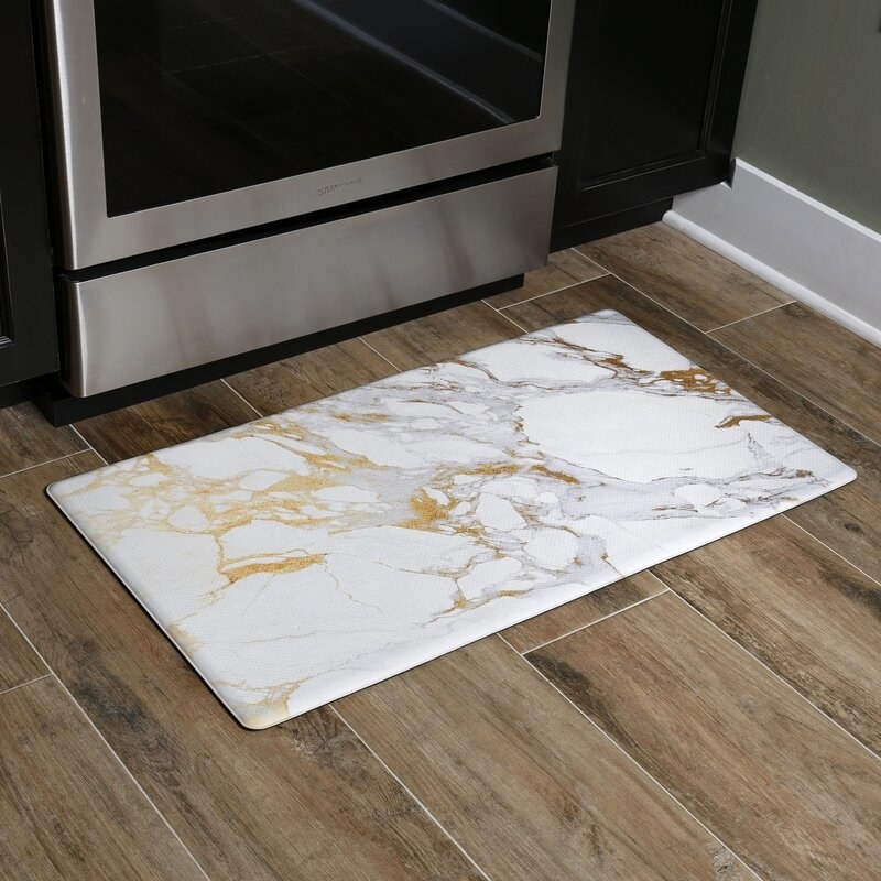 A rectangular marble-print mat laid out in front of an oven