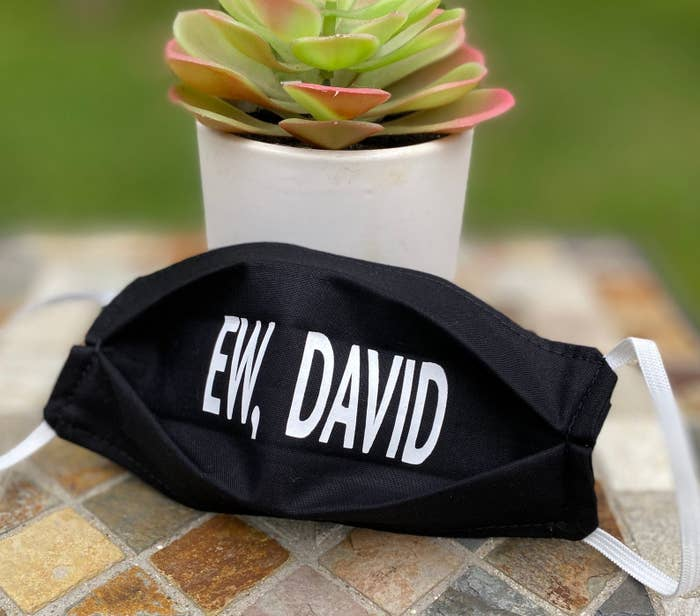 """A black face mask that says """"ew, david"""" in white"""