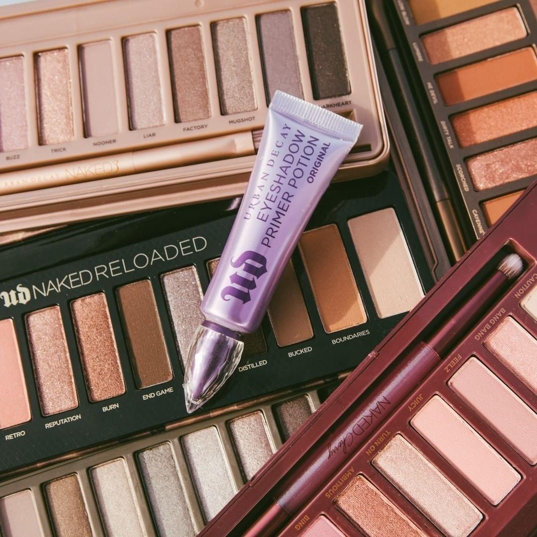 A tube of eye primer on a pile of eye makeup palettes