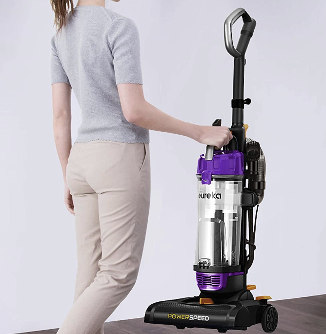 A model holding the vacuum by one of its handles