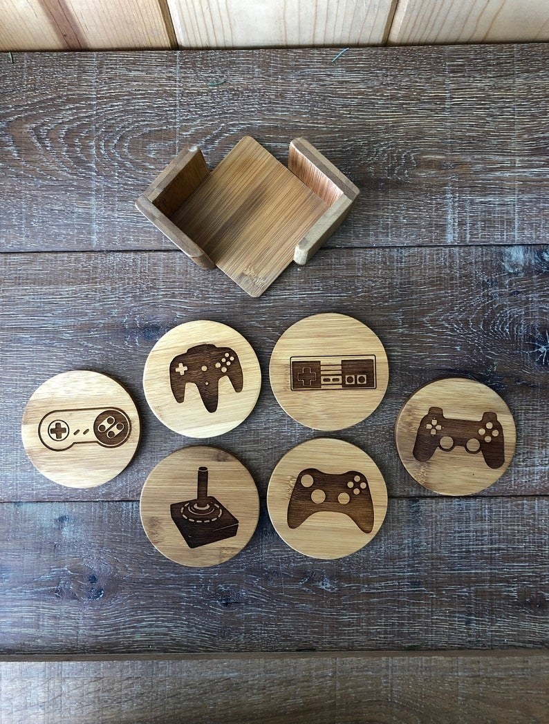 a set of wooden round coasters with different video game controllers etched onto them