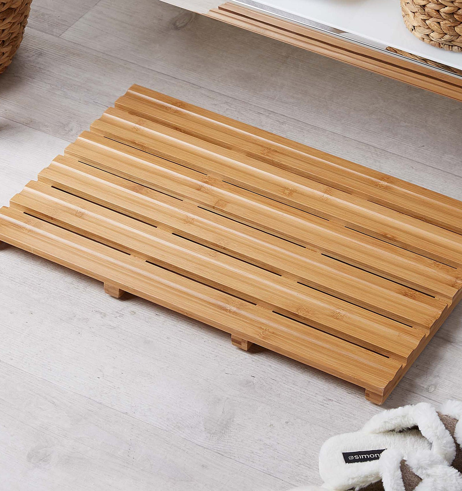 A slatted wooden bath mat in front of a bathroom sink