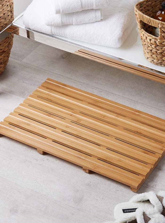 A wooden bath mat with slats next to a bath tub