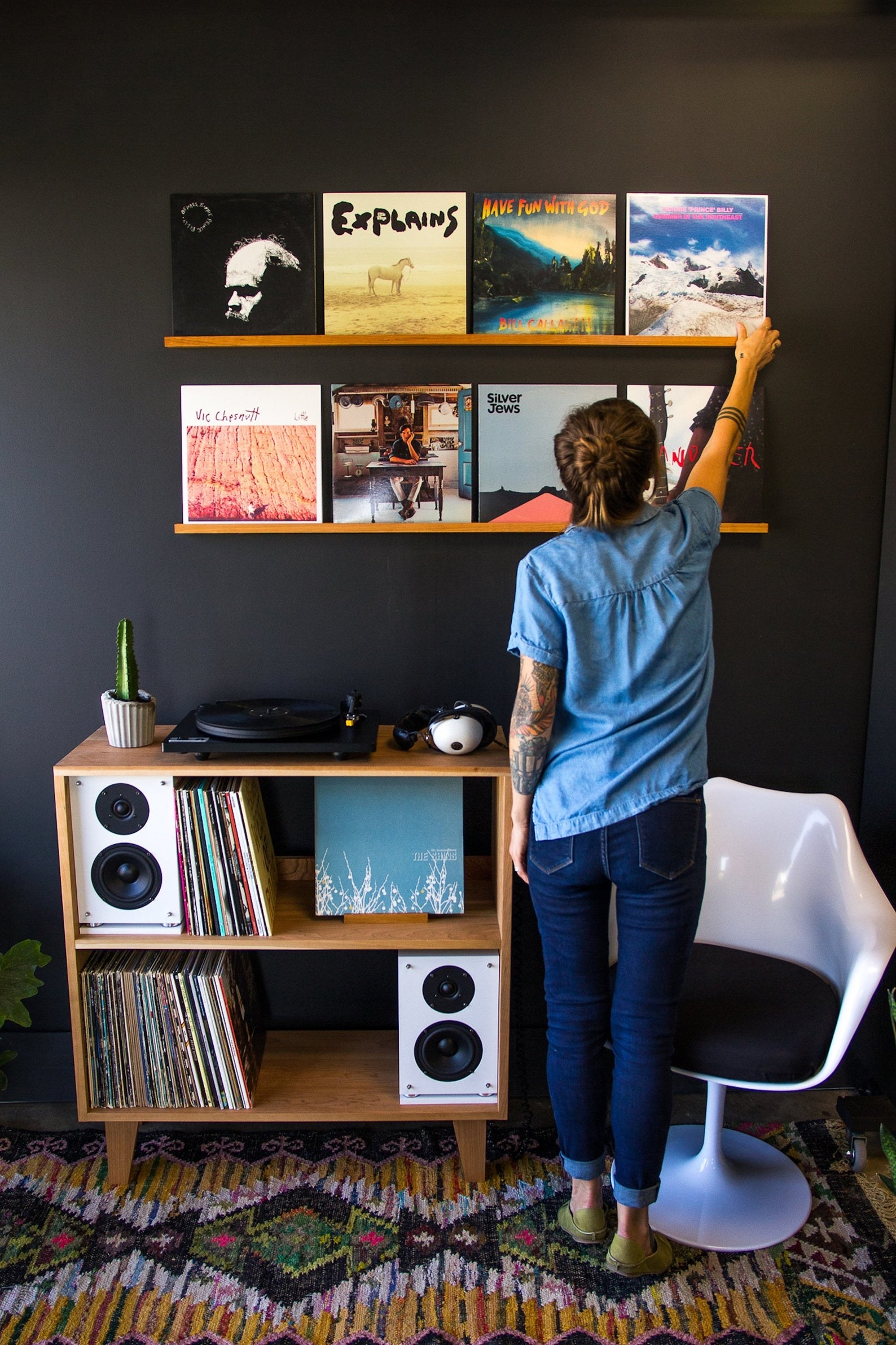 Two ledges displaying a variety of records above a record player