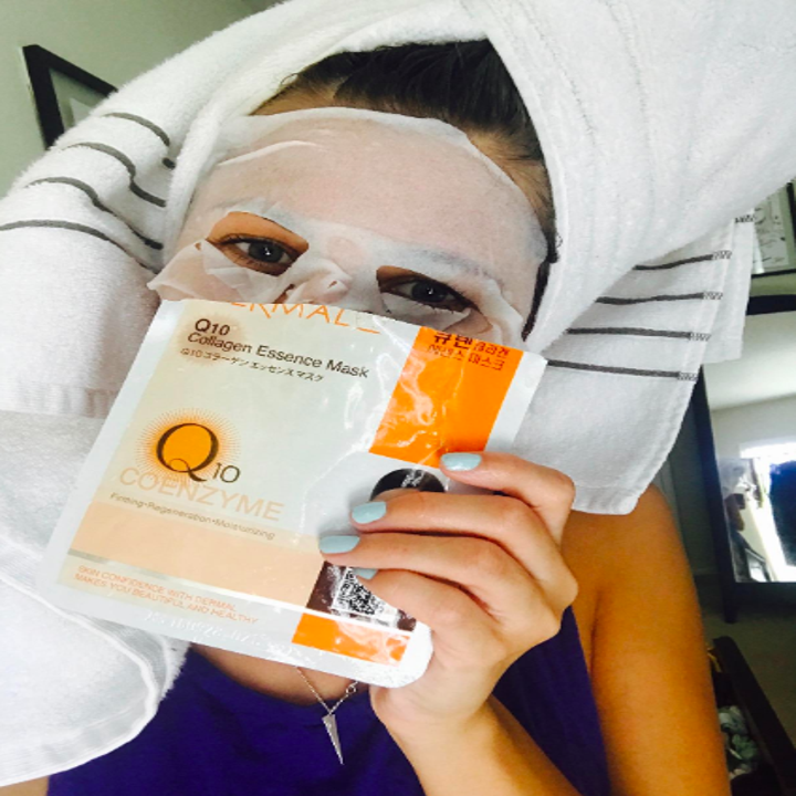 reviewer wearing the Q10 mask and holding up the package
