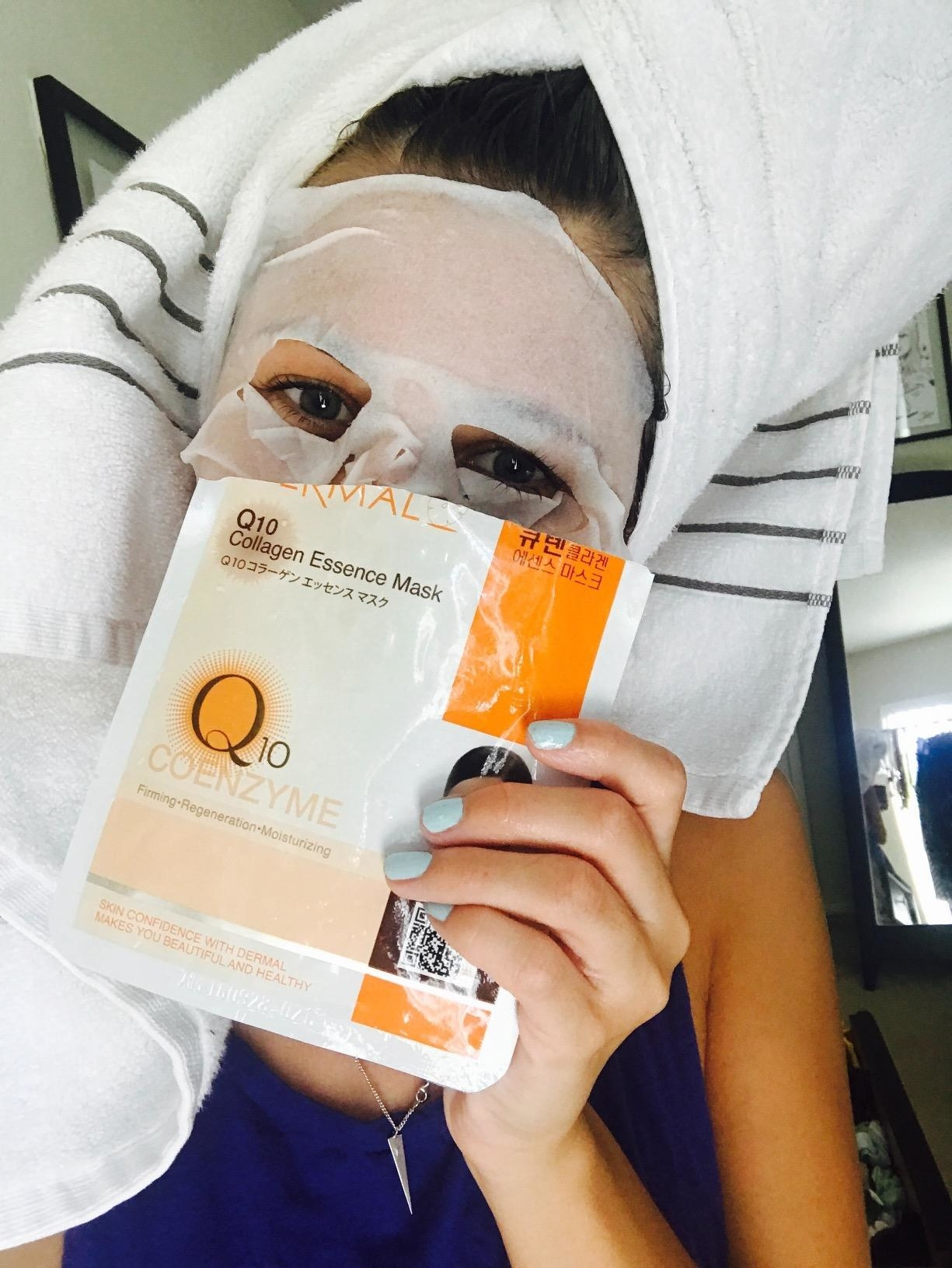 A reviewer with a sheet mask on their face holding the mask packet to the camera