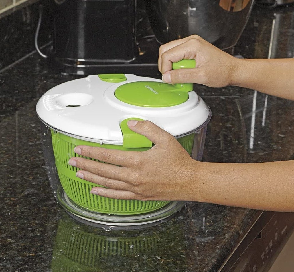 green salad spinner with white cover