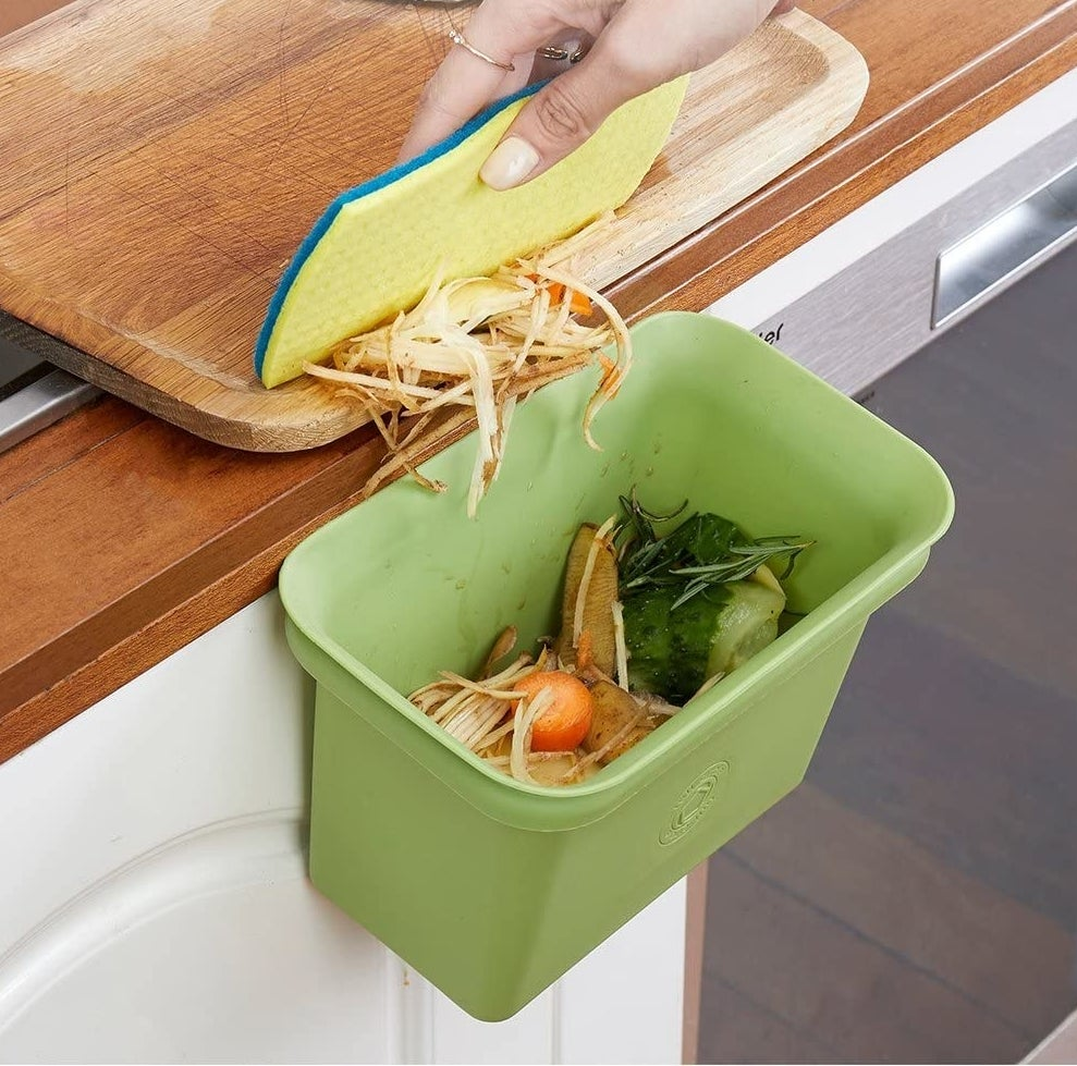 Small bin in green attached to a counter with food scrape inside of it