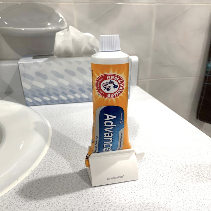 reviewer photo of the white holder with toothpaste inside