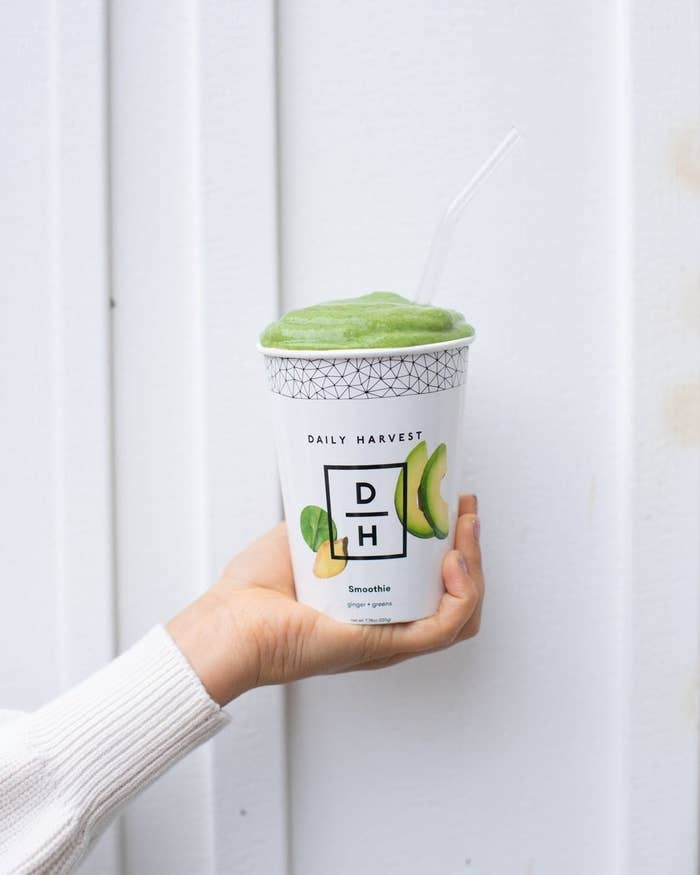 A hand holding a paper cup filled with a bright green smoothie from Daily Harvest.