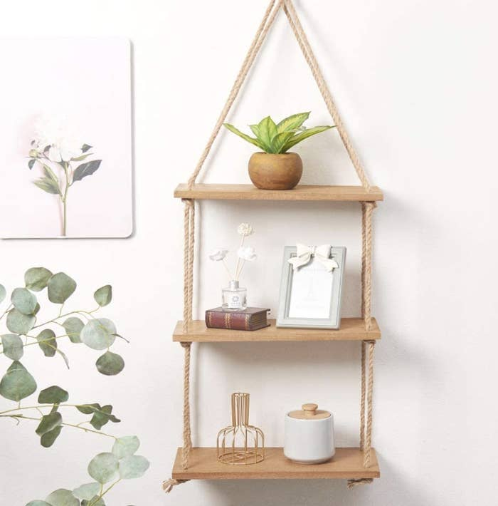 A hanging shelf filled with a tiny plant and gold sculptures on a wall