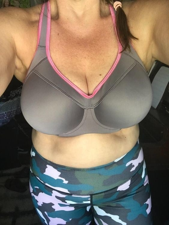 Reviewer wearing sports bra in grey with pink lining