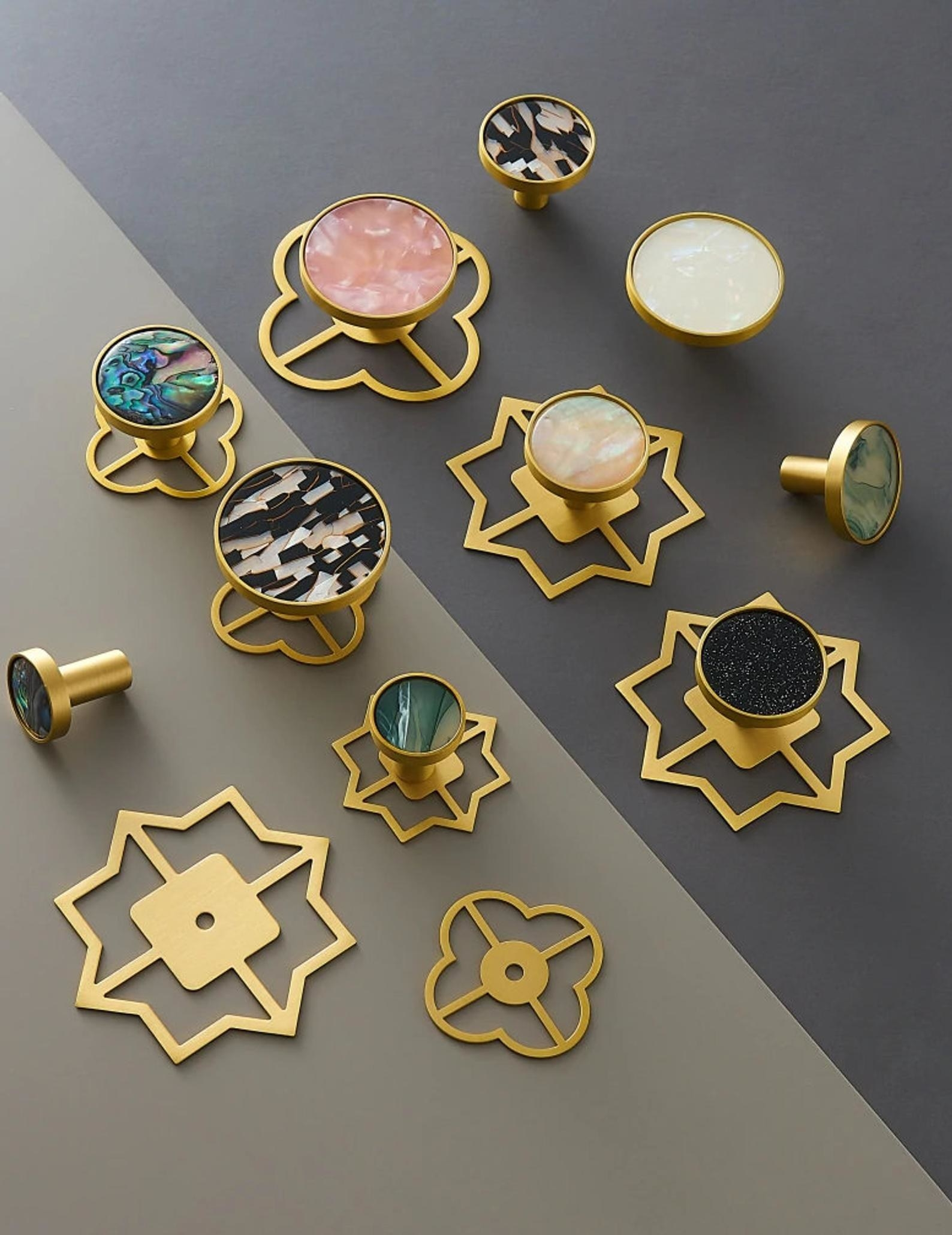 doorknobs that look more like gold that have bases in various shapes (like stars) and the handle part has different colors like pink marble, black, and green marble