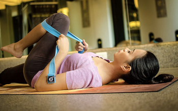 model lies on the floor to stretch with blue yoga strap