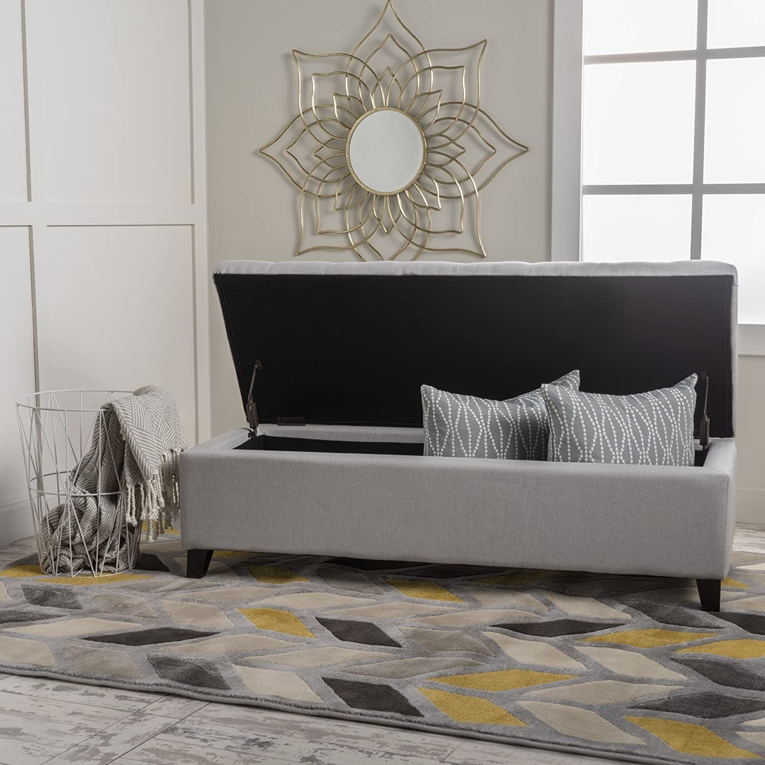 gray long storage ottoman with open top and room inside for throw pillows