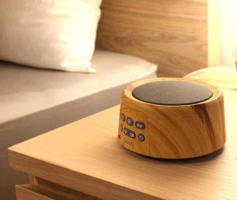 A circular white noise machine with a wooden finish and a gray speaker on top