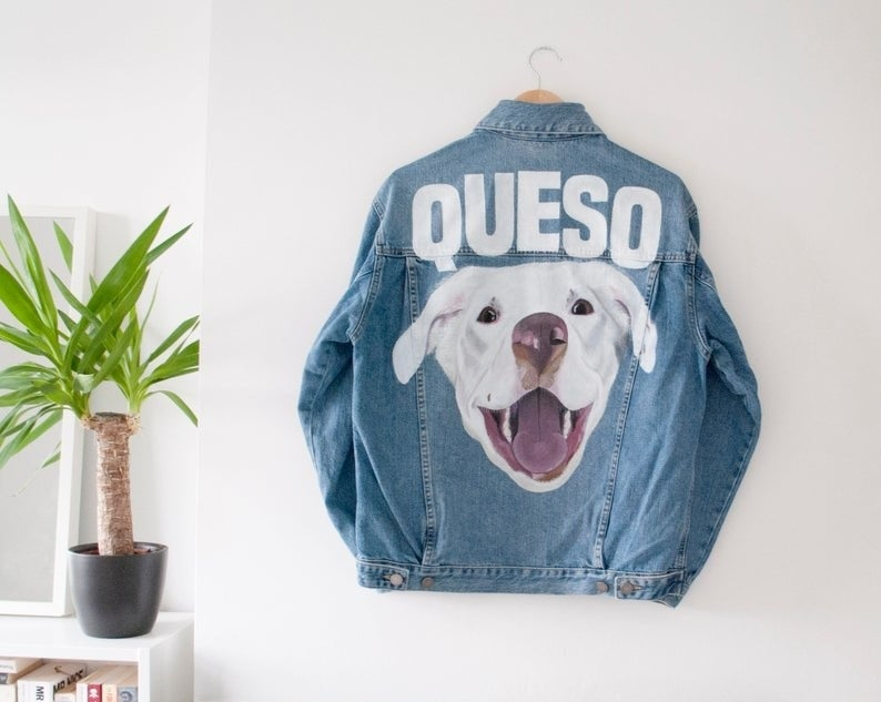 denim jacket with a hand-painted portrait of a dog and their name Queso spelled out