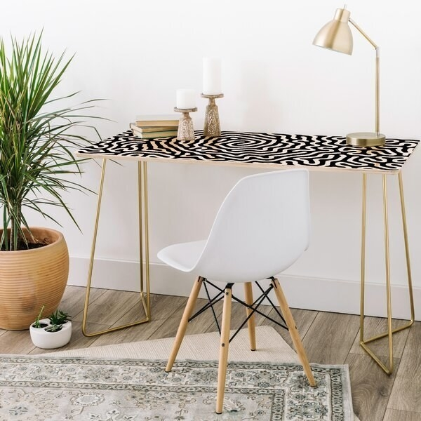 Table has a flat surface with a black and white pattern that looks like squiggly lines. The legs metal, skinny, and gold.