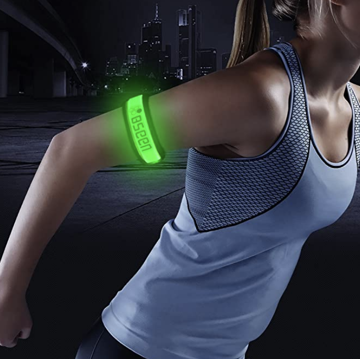 Model wears green glow-in-the-dark armbands on a night run
