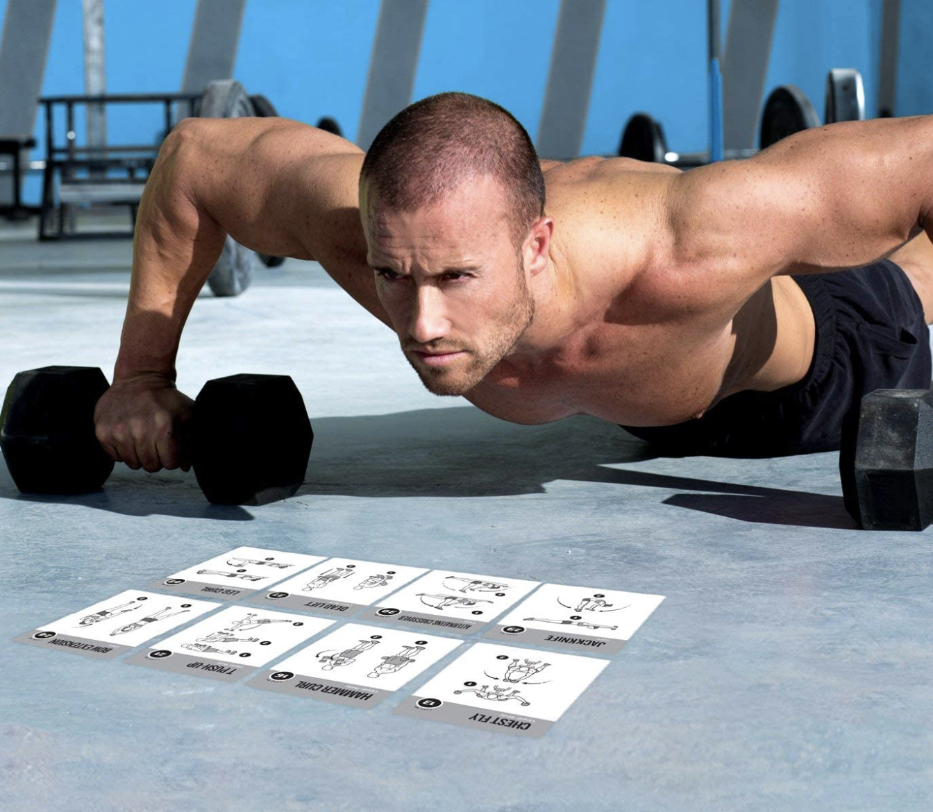 Model does a push-up with black dumbbells while reading a stack of workout cards with other exercise positions
