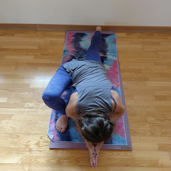 reviewer practices yoga on mat with tie-dye yoga towel on top