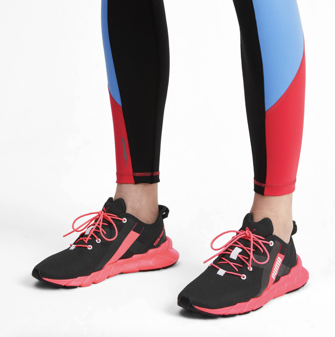 Model wears black and pink Puma training shoes with red, black, and blue striped leggings