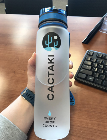 Reviewer holds same water bottle while working at a desk