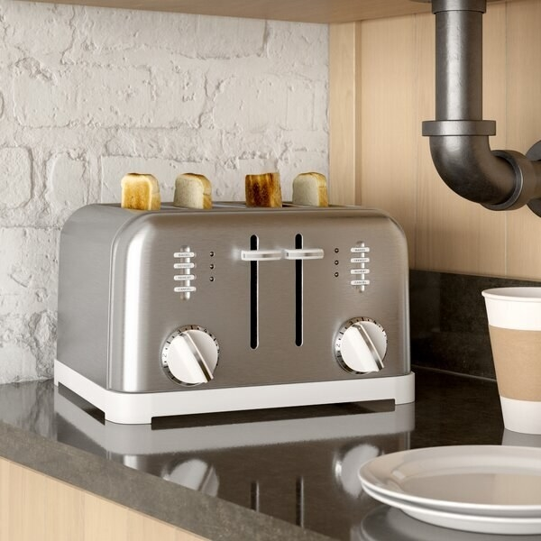 A large toaster with two sets of dials, eight toasting option buttons, and four slices of toast popping out