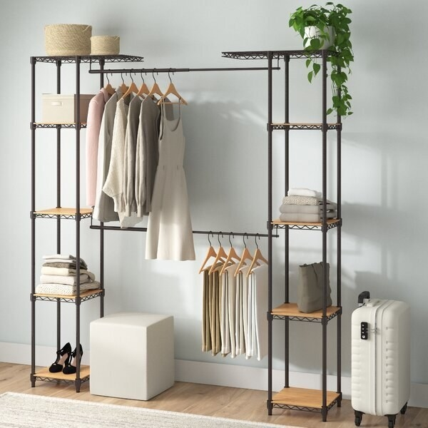 The wardrobe consisting of five shelves on each side connected by two bars. Clothing hangs from each bar, and linens, shoes, and home decor rest on the shelves