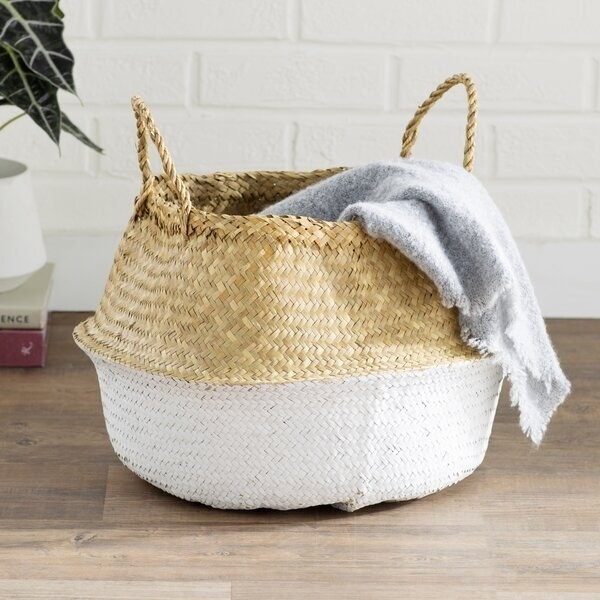 A convex-shaped wicker basket with a blanket hanging over the edge