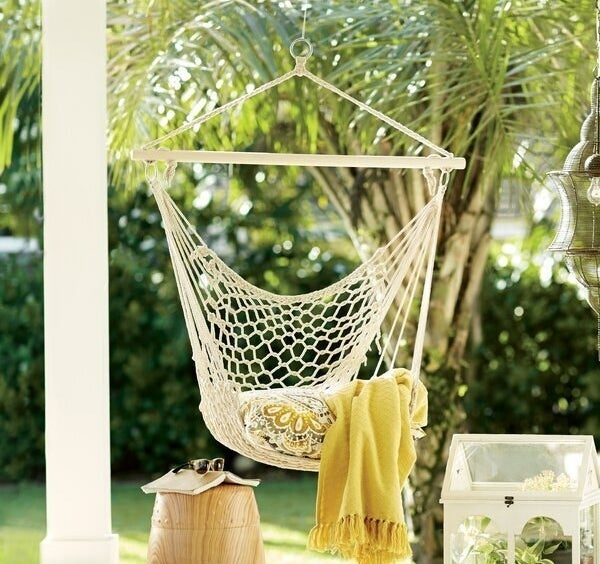 Natural wood and rope chair hammock hanging from back porch