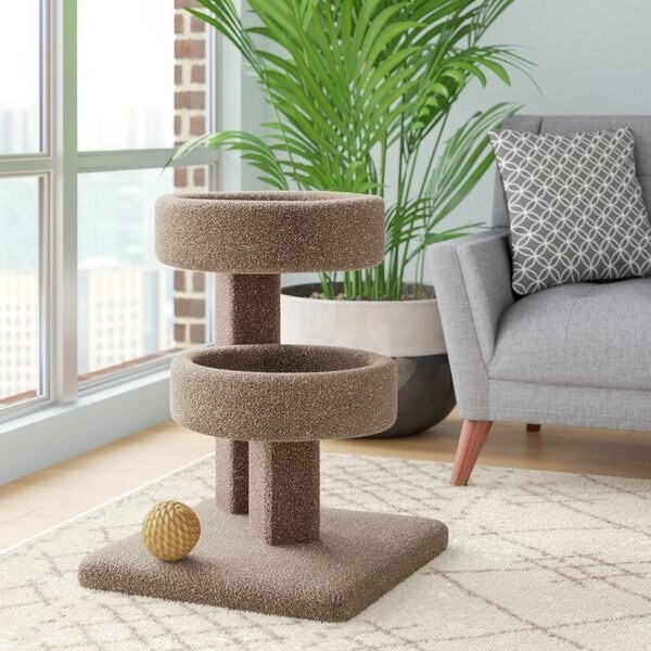 The two-tiered, carpeted cat condo with a square base set in a living room