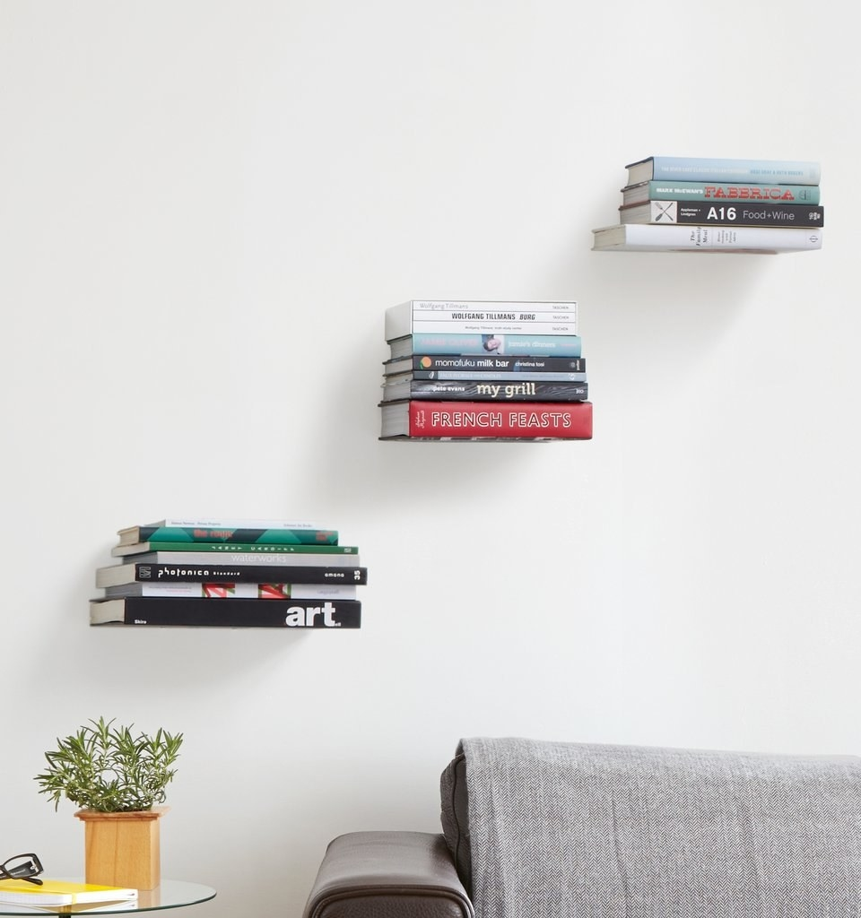 Three floating shelves mounted on wall with books