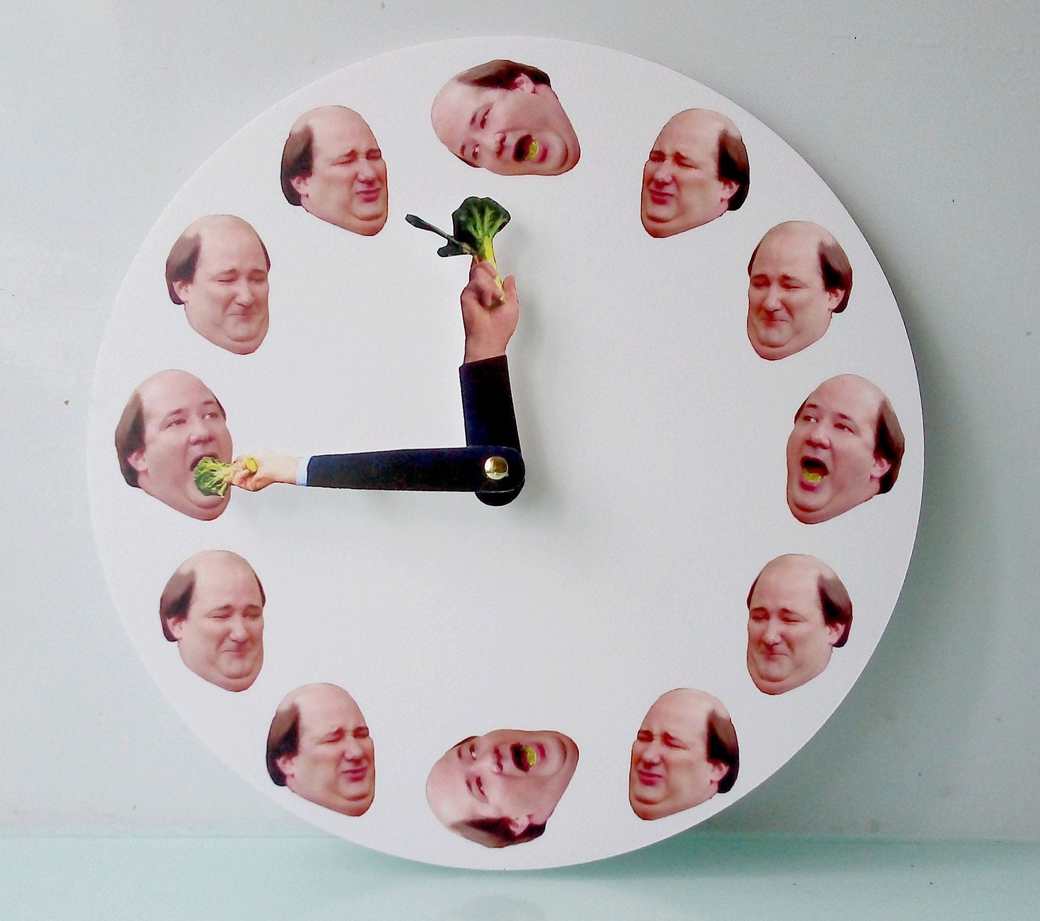 clock with pictures of heads of kevin malone with two clock arms holding broccoli